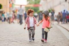 Pojke och flicka som går på gatan Fotografering för Bildbyråer