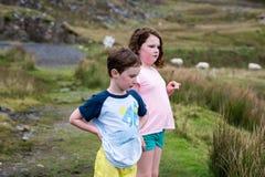 Pojke och flicka som går upp de Slieve ligaklipporna, ståndsmässiga Donegal, Irland Arkivfoto