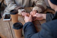 Pojke och flicka som håller sig fingrar med kaffe royaltyfri foto