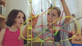 Pojke och flicka som hemma bygger ett torn från leksaker arkivfilmer