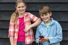 Pojke och flicka som ler barn som använder mobiltelefonen royaltyfri bild