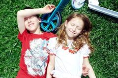 Pojke och flicka som ler lögn på gräset Royaltyfria Foton
