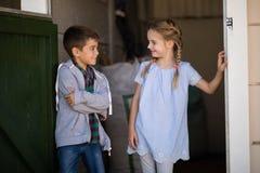 Pojke och flicka som ler på de i stallet royaltyfri bild