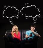 Pojke och flicka som separat sitter med smarthones Royaltyfri Fotografi