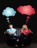 Pojke och flicka som separat sitter med smarthones Arkivfoton