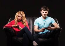 Pojke och flicka som separat sitter med smartphones Arkivbilder
