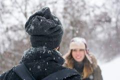 Pojke och flicka som ser de i snön Arkivfoton
