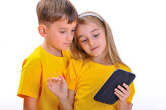 Pojke och flicka som ser e-boken Royaltyfri Bild