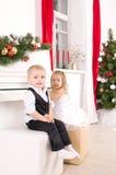 Pojke och flicka som sitter nära det vita pianot Royaltyfria Foton