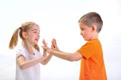 Pojke och flicka som skjuter med händer Arkivbild