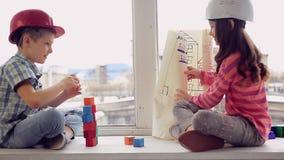 Pojke och flicka som spelar byggm?stare p? bakgrunden av en gammal fabrik lager videofilmer