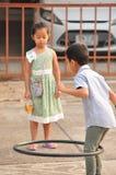 Pojke och flicka som spelar hulabeslaget på gatan i stad arkivbilder
