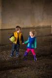 Pojke och flicka som spelar i gyttja Arkivfoto