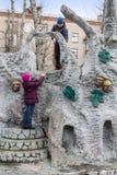 Pojke och flicka som spelar i lekplatsen Arkivbild