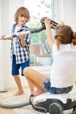 Pojke och flicka som spelar med dammsugare Arkivfoton