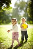 Pojke och flicka som spelar med den gula bollen Arkivfoton