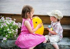 Pojke och flicka som spelar med en Toy Easter Chick Arkivbild
