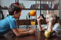 Pojke och flicka som spelar med exponeringsglas och frukter på kök tillsammans Arkivfoton