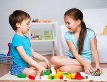 Pojke och flicka som spelar med leksaker Royaltyfria Bilder
