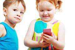 Pojke och flicka som spelar med mobilen Arkivfoto