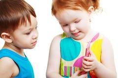 Pojke och flicka som spelar med mobilen Royaltyfri Bild