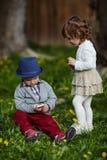 Pojke och flicka som spelar med mobiltelefonen Royaltyfri Foto