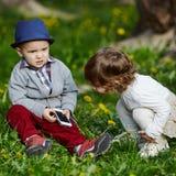 Pojke och flicka som spelar med mobiltelefonen Arkivfoto