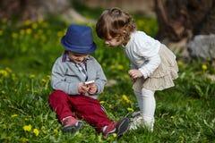 Pojke och flicka som spelar med mobiltelefonen Arkivbild