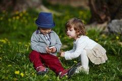 Pojke och flicka som spelar med mobiltelefonen Arkivbilder