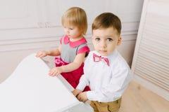 Pojke och flicka som spelar på pianot royaltyfri bild