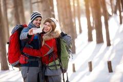 Pojke och flicka som tar fotoet i snöig natur Arkivfoto