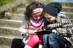 Pojke och flicka som tillsammans använder minnestavlan Royaltyfri Fotografi