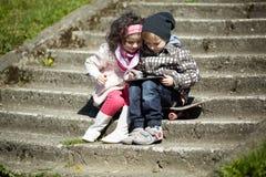 Pojke och flicka som tillsammans använder minnestavlan Arkivfoton