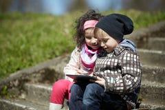 Pojke och flicka som tillsammans använder minnestavlan Arkivbild