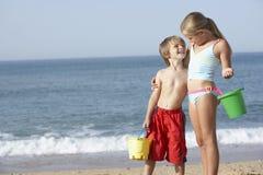 Pojke och flicka som tycker om strandferie Royaltyfri Bild