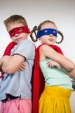 Pojke- och flickaanseende med den korsade och låtsa armen för att vara en superhero Royaltyfri Bild