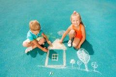 Pojke- och flickaattraktionkrita avbildar sammanträdetoggether Arkivfoton