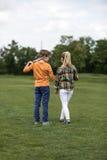 Pojke- och flickainnehavhänder, medan stå på det gröna fältet, hållande badmintonracket för pojke på hans skuldra Arkivbilder