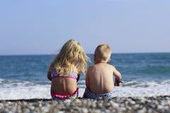 Pojke- och flickasammanträde på stranden Arkivbild