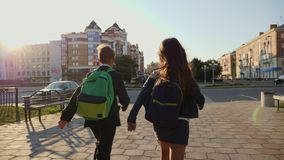 Pojke- och flickaspring med ryggsäckar som är sena lager videofilmer
