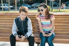Pojke- och flickatonåringar som spelar, läsning som ser smartphonen På bänken stads- bakgrund arkivfoton