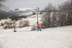 Pojke- och flickautförsåkning skidar på semesterorten i solig dag för vinter, Montenegro, Zabljak, 10:41 2019-02-10 royaltyfri foto