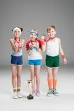 Pojke och flickor med medaljer och mästarebägaren på grå färger Arkivfoto