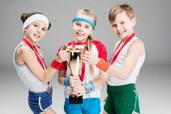 Pojke och flickor med medaljer och mästarebägaren på grå färger Arkivbilder