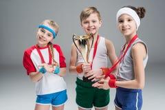 Pojke och flickor med medaljer och mästarebägaren på grå färger Royaltyfri Fotografi