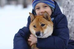 Pojke och gullig hund på att gå för vinter Fotografering för Bildbyråer