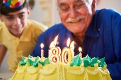 Pojke och hög man som blåser stearinljus på kakafödelsedagpartiet Royaltyfria Bilder