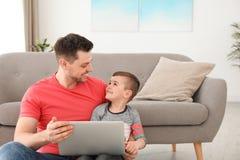 Pojke och hans fader med b?rbara datorn som sitter n?ra soffan p? golv arkivfoto