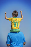 Pojke och hans fader som ser upp på den brasilianska flaggan royaltyfria bilder