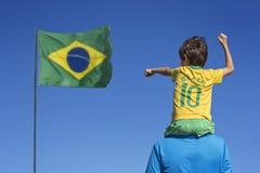 Pojke och hans fader som ser upp på den brasilianska flaggan royaltyfri foto
